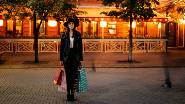 Time-lapse-of-young-woman-shopaholic-standing-outdoors-in-the-street-with-shopping-bags-and-looking-at-camera-while-flow-of-people-is-moving-around-her-