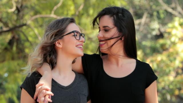 Zwei-Freundinnen-zusammen-zu-Fuß-in-den-Park-umarmen-und-küssen-einander-LGBT-paar-zu-küssen-
