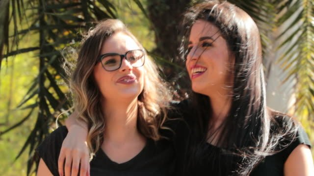 Zwei-Freundinnen-zusammen-zu-Fuß-in-den-Park-umarmen-einander-LGBT-paar