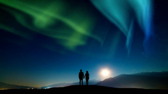 The-couple-standing-on-a-mountain-against-a-sky-with-northern-light-time-lapse