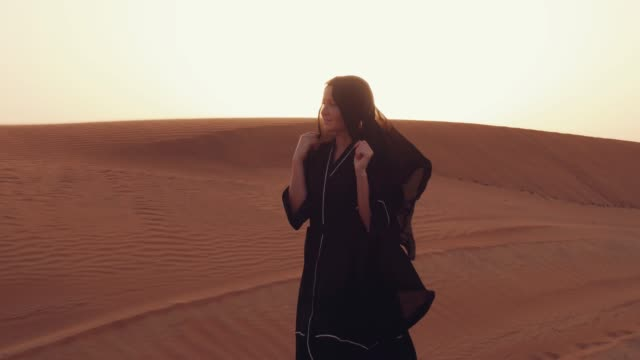 Muslim-woman-standing-near-mosque-in-the-desert-Strong-wind-Middle-East-peace-without-war