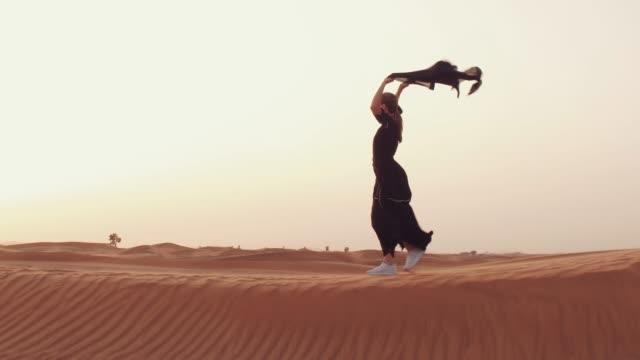 Muslimische-Frau-steht-in-der-Nähe-von-Moschee-in-der-Wüste-Starker-Wind-Nahostfrieden-ohne-Krieg