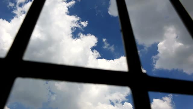 Barras-de-celda-de-prisión-y-cielo-azul-pan-shot