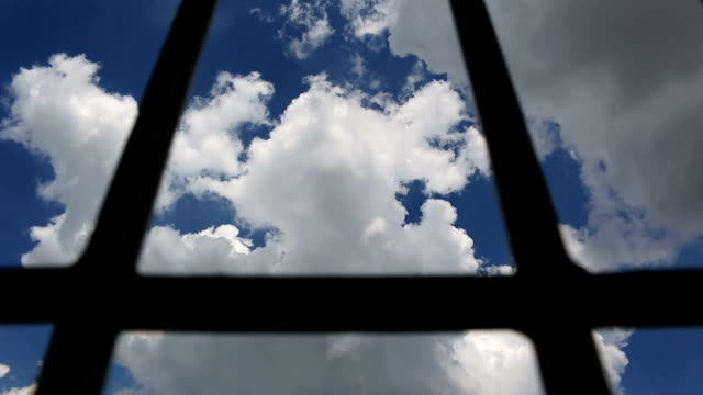 Prison-bars-and-blue-sky-dolly-shot