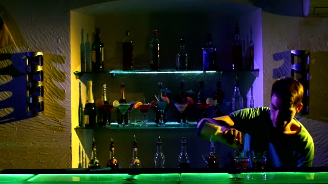 Professional-barman-making-cool-amazing-tricks-using-bottle-juggling-standing-behind-the-bar-catching-throwing-up-and-pouring-two-liquids-slow-motion