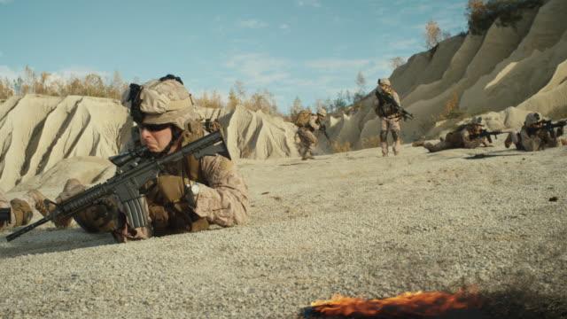 Escuadrón-de-soldados-completamente-equipados-y-armados-arrastrándose-durante-operación-militar-en-el-desierto-Cámara-lenta-