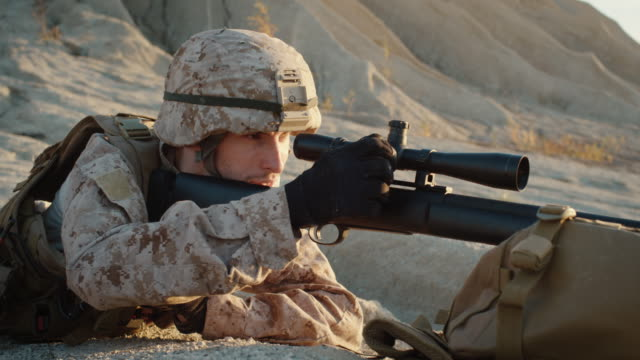 Close-up-of-Sniper-Lies-Down-on-the-Hill-and-Aims-through-the-Rifle-Scope-in-Desert-Environment