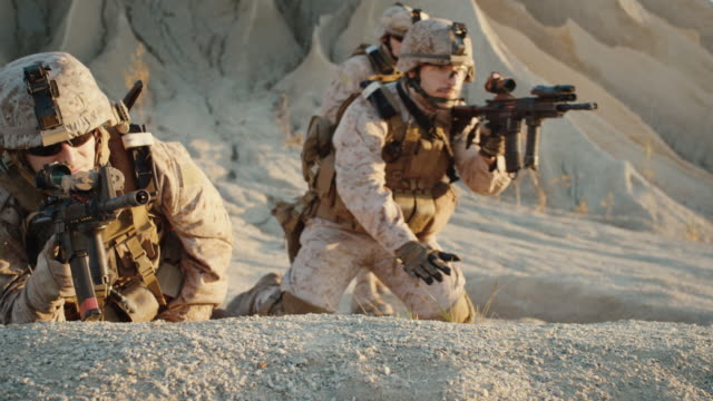 Grupo-de-soldados-Acuéstese-en-la-colina-apunte-a-través-del-alcance-del-rifle-de-asalto-en-medio-del-desierto-Cámara-lenta-