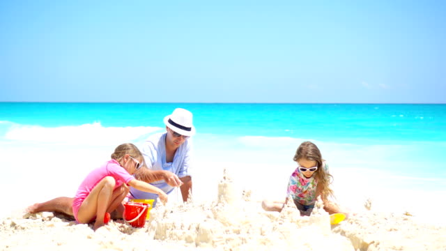 Padre-y-los-niños-haciendo-castillos-de-arena-en-la-playa-tropical