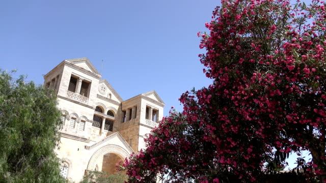 Copas-de-los-árboles-en-flor-y-enorme-iglesia-detrás