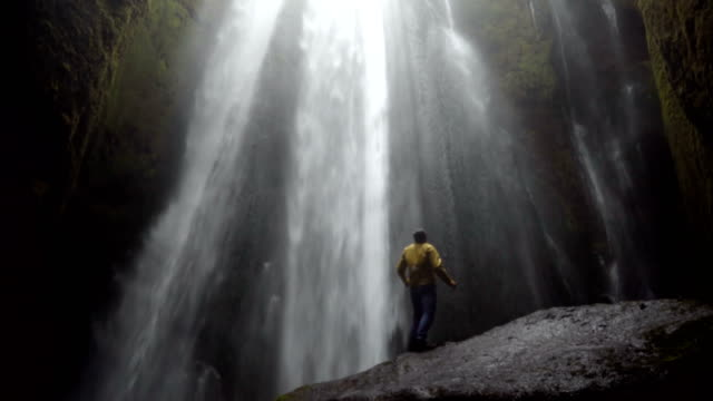 Young-traveling-man-walking-near-the-powerful-Gljufrabui-waterfall-in-Iceland-Male-jumping-of-joy-and-happy