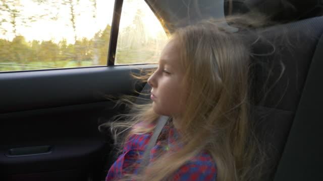 Junge-schöne-Mädchen-auf-Abenteuerreise-Auto-den-Wind-in-ihrem-Haar-Ziemlich-schwere-weiße-Mädchen-Straße-Geschwindigkeit-Antrieb-starker-Wind-Reisen-Herbst-Sonnenuntergang-Hinterleuchtete-hellen-Sonnenstrahl-