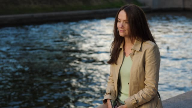 Thoughtful-business-woman-looking-on-water