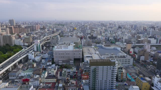 Aerial-panorama-of-Osaka-City-Busy-road-and-railway-traffic-Shinsekai-downtown-area-from-top-