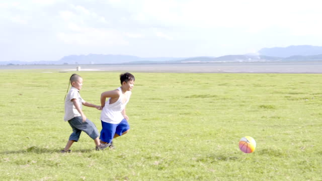 Two-Asian-boys-Playing-football-fun-happy-The-rural-prairie-background-Video-4K-Slow-motion