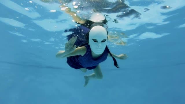Una-inusual-niña-nada-y-poses-bajo-el-agua-en-una-fabulosa-máscara-blanca-y-un-vestido-púrpura-mira-la-cámara-y-agitando-sus-manos-sobre-un-fondo-azul-Cámara-lenta-