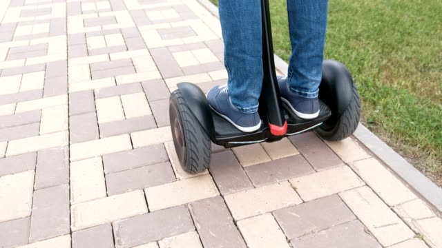 Person-s-legs-in-sneakers-rolling-on-gyro-scooter-on-paving-road-