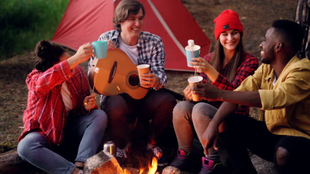 Joyful-young-people-friends-are-clinking-glasses-with-drinks-sitting-around-fire-in-forest-with-warm-marshmallow-on-sticks-smiling-man-is-holding-guitar-