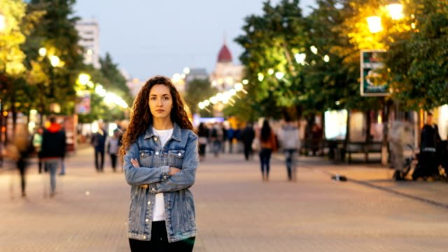 Time-lapse-portrait-of-lonely-young-lady-standing-in-street-downtown-with-arms-crossed-while-crowds-of-men-and-women-are-passing-by-Loneliness-and-time-concept-