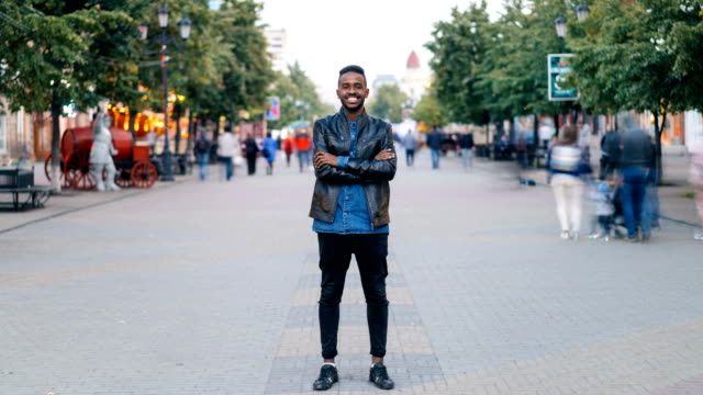 Time-lapse-portrait-of-cheerful-African-American-man-standing-in-city-center-wearing-stylish-clothes-looking-at-camera-and-smiling-while-people-are-passing-by-