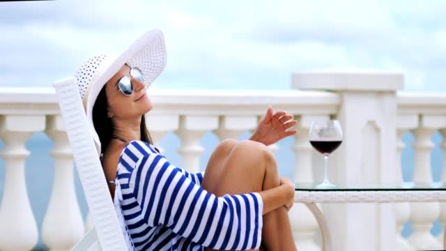 Elegante-mujer-en-gafas-de-sol-y-sombrero-en-el-balcón-sentado-en-silla-abrazando-las-piernas-de-manos-cruzadas