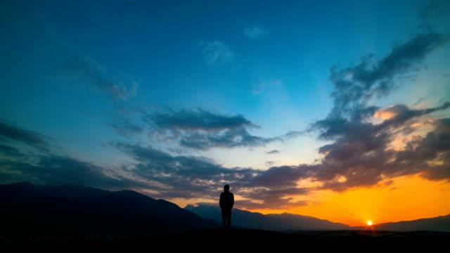 El-hombre-de-pie-sobre-una-montaña-contra-una-puesta-de-sol-con-la-luz-del-norte-lapso-de-tiempo