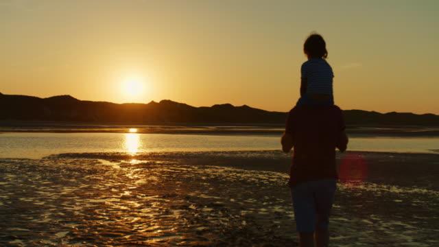 Silhouette-der-Vater-mit-Sohn-auf-seinen-Schultern-am-Strand-zu-Fuß