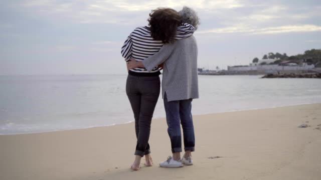 Glückliche-senior-Mutter-und-Erwachsene-Tochter-umarmt-am-Sandstrand-
