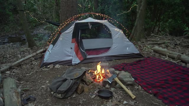 Bushcraft-camp-site-in-the-wilderness-with-campfire-axe-and-blanket-