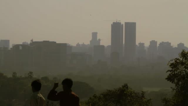 Two-men-walking-past-Mumbai-skyline-viewpoint-