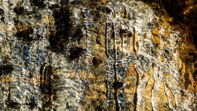 Primer-plano-de-hielo-de-fusión-en-Rockface-con-gotas-de-agua-corriente