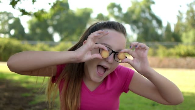 Happy-teenage-girl-closing-her-eyes-with-round-cookies-and-making-fun