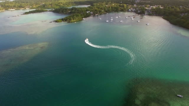 Flying-over-motor-boat-sailing-in-bay-Mauritius-Island