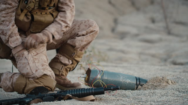 Soldier-Defusing-a-Bomb-by-Cutting-a-Wire-During-Military-Operation-in-Desert-Environment