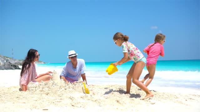 Familie-mit-zwei-Kindern-machen-Sandburg-am-tropischen-Strand