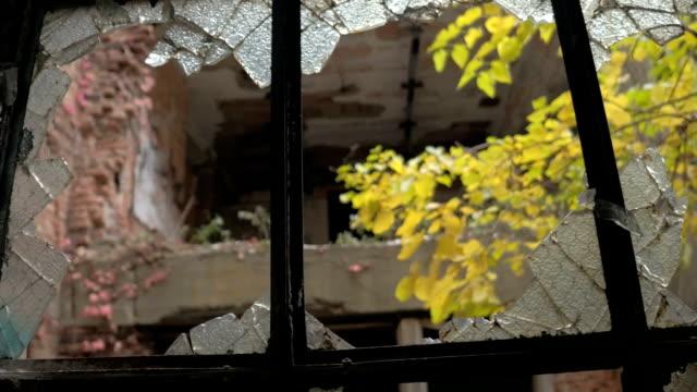FPV:-Mirando-por-la-ventana-rota-en-un-edificio-abandonado-en-pueblo-fantasma-que-se-decae