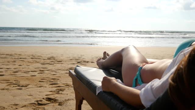 Mujer-joven-acostado-en-la-hamaca-junto-al-mar-y-bronceado-Cuerpo-de-la-mujer-en-el-diván-relajarse-y-disfrutar-durante-las-vacaciones-de-verano-en-la-playa-mar-arena-vacía-Chica-en-bikini-en-un-resort-Cierre-para-arriba