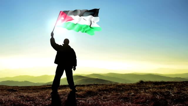 Erfolgreiche-Silhouette-Mann-Sieger-winken-Jordan-Flagge-auf-die-Bergspitze-Cinemagramm-LOOP-Hintergrund