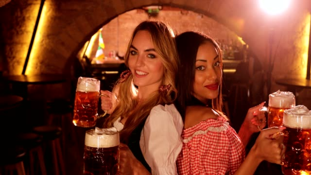 Young-multi-ethnic-women-in-Bavarian-costumes-celebrating-Oktoberfest-with-beer