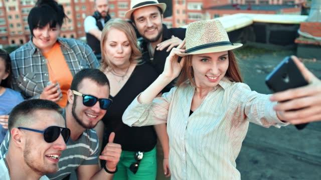 Elegante-mujer-joven-con-sombrero-tomando-selfie-rodeado-de-amigos-con-smartphone-en-fiesta-en-la-azotea