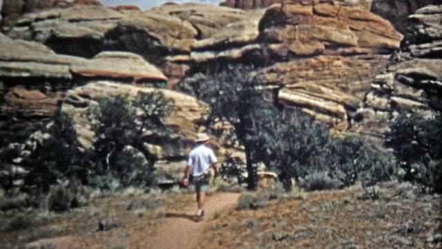 DE-CANYONLANDS-UTAH--1971:-Hombre-caminatas-estrecho-canyon-senderos-formaciones-rocosas-