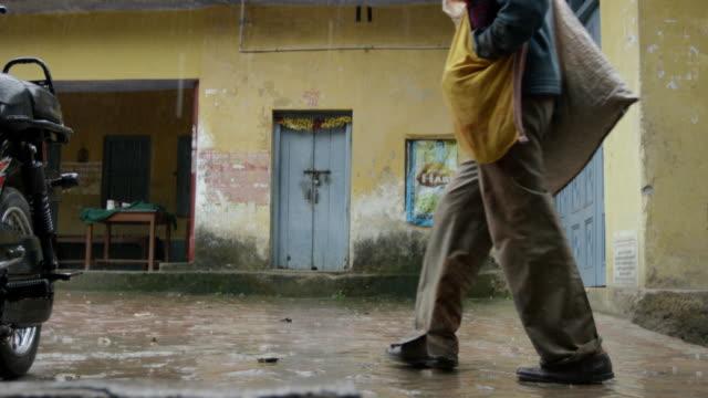 Hombre-de-pasar-una-lluvia-callejón-posterior-