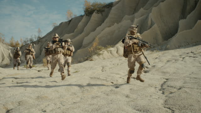 Squad-of-Fully-Equipped-Armed-Soldiers-Running-in-the-Desert-Show-Motion-