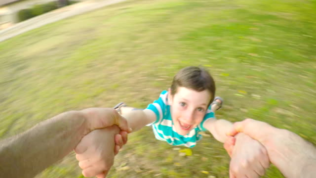 POV-footage-of-father-swinging-his-son-outdoors