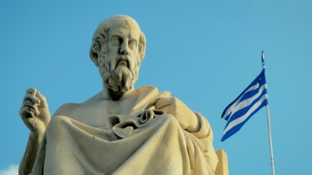 Primer-plano-de-una-estatua-de-mármol-del-gran-erudito-griego-de-la-antigüedad-de-Platón-en-el-fondo-de-la-bandera-nacional-de-Grecia-