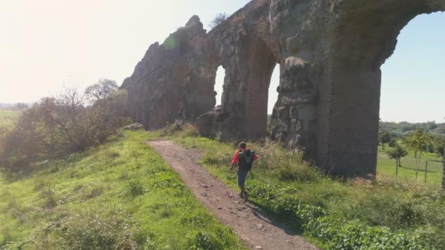 Hombre-joven-mochilero-caminando-por-camino-de-tierra-a-lo-largo-del-antiguo-acueducto-romano-en-naranja-ropa-deportiva-senderismo-dolly-de-drone-de-vista-aérea