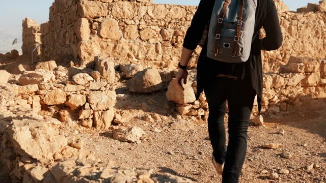 Hombre-con-pasos-de-mochila-en-paredes-antiguas-ruinas-Turismo-hombre-caucásico-caminatas-sobre-grandes-rocas-amarillas-Masada-Israel-4K