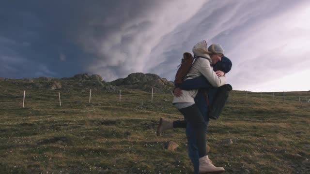 Junge-Liebende-paar-umarmt-im-Feld-Hintergrund-der-epische-dramatische-Wolken-Zeitlupe