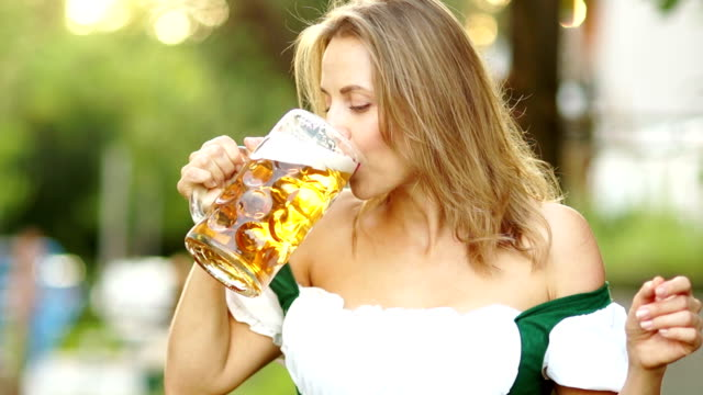 Musical-Oktoberfest-beer-festival-Mature-woman-in-a-traditional-Bavarian-suit-drinks-beer-and-embarrassingly-wipes-the-foam-on-her-lips-Red-lips-sexy-erotic