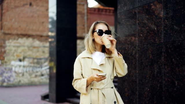 Elegante-dama-joven-está-caminando-por-la-calle,-uso-de-teléfono-inteligente-y-beber-para-llevar-a-pie-disfrutando-de-café-en-la-hermosa-ciudad-moderna.-Personas,-estilo-de-vida-moderno-y-el-concepto-de-bebidas-para-llevar.